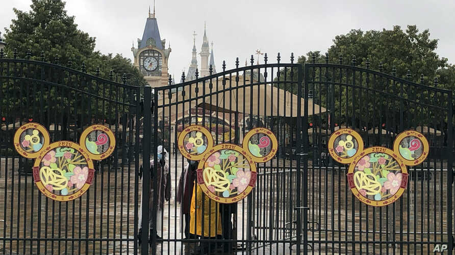 Employees stand at the gates of the Shanghai Disney Resort, which announced that it will be closed indefinitely from Saturday, in Shanghai, Jan. 25, 2020.