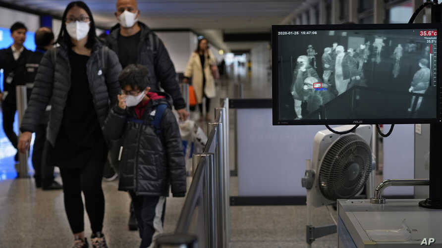 Health surveillance officer use temperature scanner to monitor passengers arriving at Hong Kong International Airport in Hong Kong, Jan. 25, 2020.