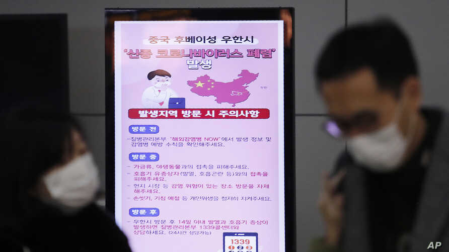 FILE - A poster warning about coronavirus is seen as passengers wear masks in a departure lobby at Incheon International Airport in Incheon, South Korea, Jan. 27, 2020.