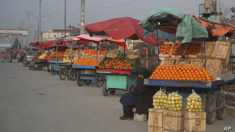 FILE - An Afghan fruit vendor waits for customers in the street in Kabul, Afghanistan, Jan. 19, 2020. Afghanistan will need vast amounts of foreign funding to keep its government afloat through 2024, a U.S. agency said.