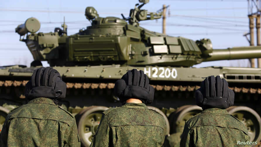 Russian tank crew members wait for their T-72B tank to be ready to move off a train shortly after Russian tanks arrived