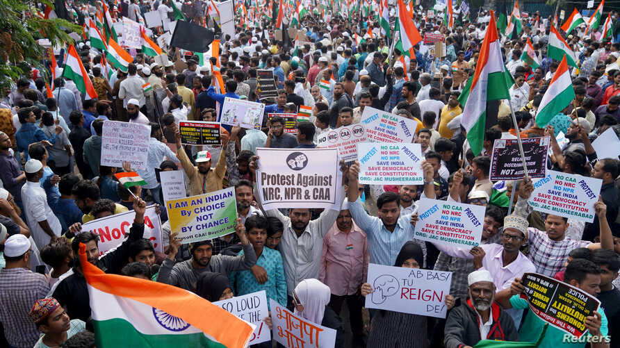 Demonstrators hold placards and flags as they attend a protest rally against a new citizenship law, in Hyderabad, India, Jan. 4, 2020.