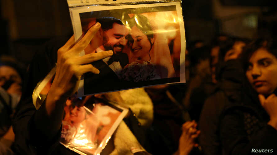 A woman holds a picture of newlyweds, victims of the crash of the Boeing 737-800 plane, flight PS 752, as people gather to show…