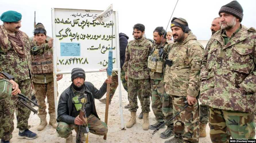 "Afghan security forces posing to camera in front of a so-called Afghanistan Islamic Emirates custom house sign the reads ""Do no pass without custom house tariff. Jan. 13. 2020. (Photo courtesy of Afghan Ministry of Defense)"
