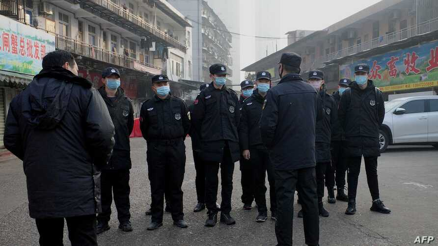 Security guards stand in front of the closed Huanan wholesale seafood market, where health authorities say a man who died from a respiratory illness, had purchased goods from, in the city of Wuhan, Hubei province, China, Jan. 12, 2020.