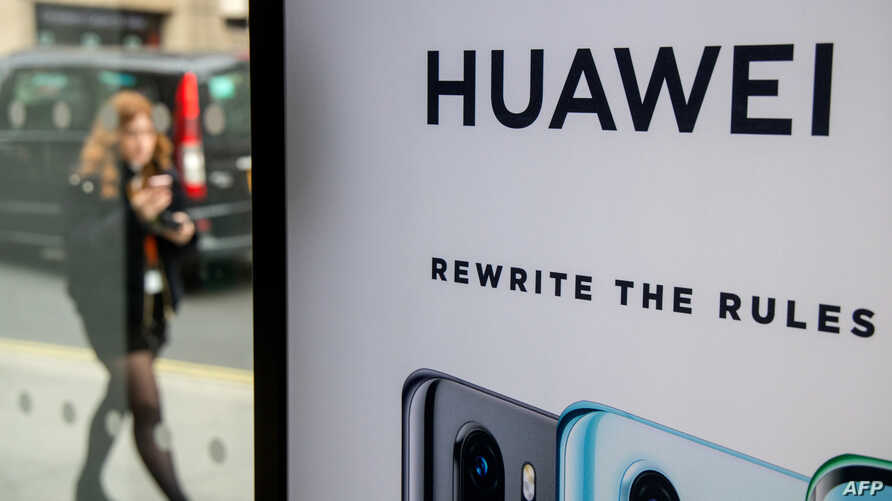 FILE - A pedestrian walks past a Huawei product stand at an EE telecommunications shop in central London, Britain, April 29, 2019.