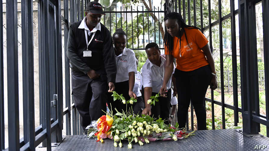 FILE - Members of Emergency Rescue Services place flowers during the reopening ceremony of the DusitD2 hotel, in Nairobi, Kenya, July 31, 2019, six months after the terror attack that left 21 people dead.