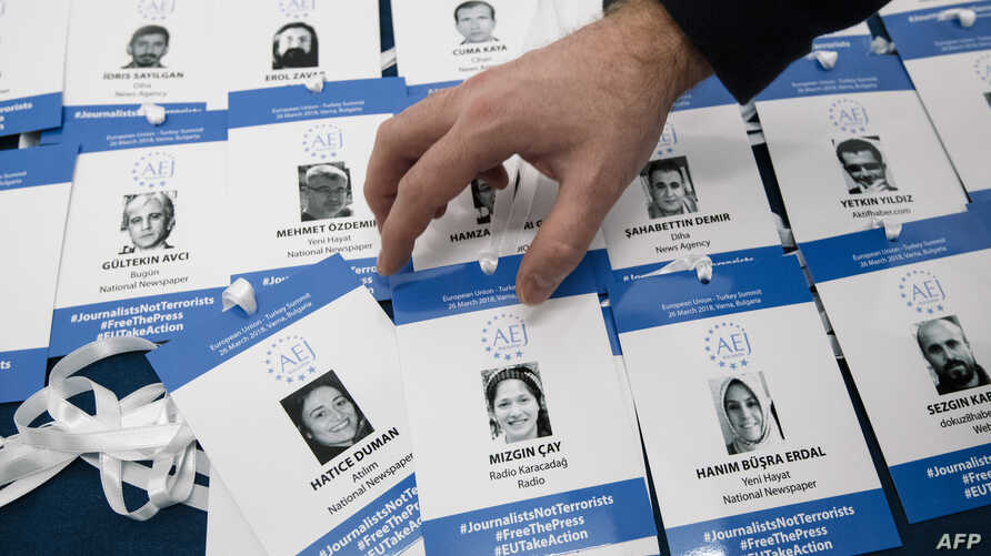 FILE - An activist arranges symbolic press passes with the names, pictures and media affiliations of Turkish journalists accused by the Turkish government of having aided a failed 2016 coup, during a protest in Sofia, Bulgaria, March 22, 2018.