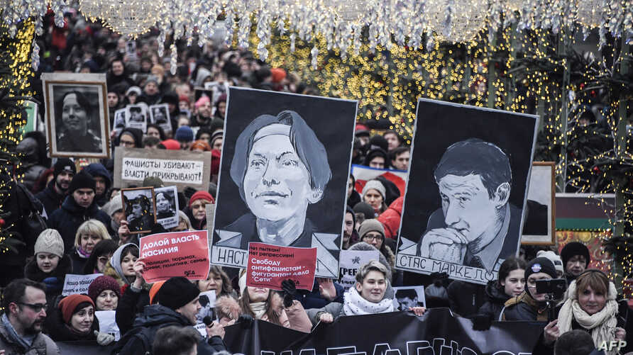 Russian opposition protestors march in central Moscow, Jan. 19, 2020, carrying portraits of lawyer Stanislav Markelov and journalist Anastasia Baburova.