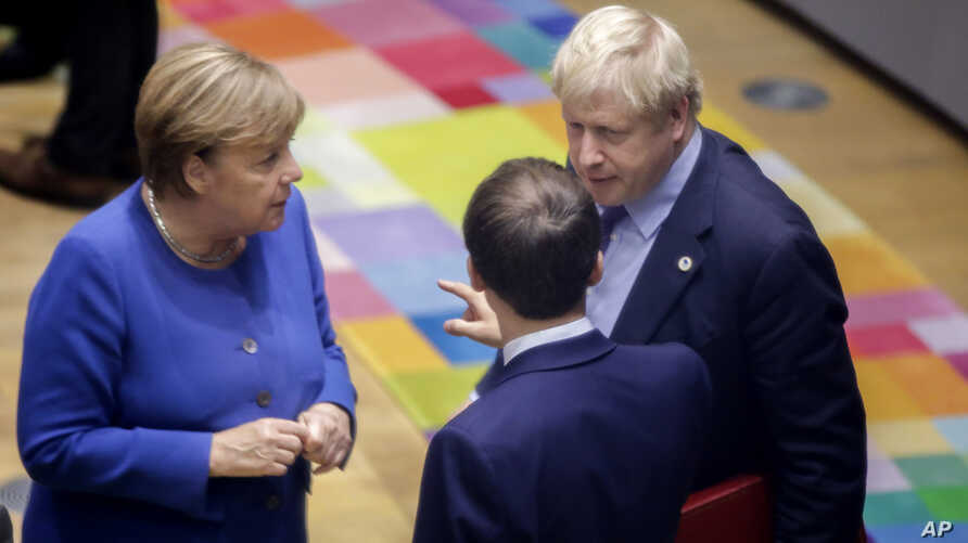 FILE - British Prime Minister Boris Johnson, right, speaks with German Chancellor Angela Merkel, left, and French President Emmanuel Macron during an EU summit in Brussels, Oct. 17, 2019.