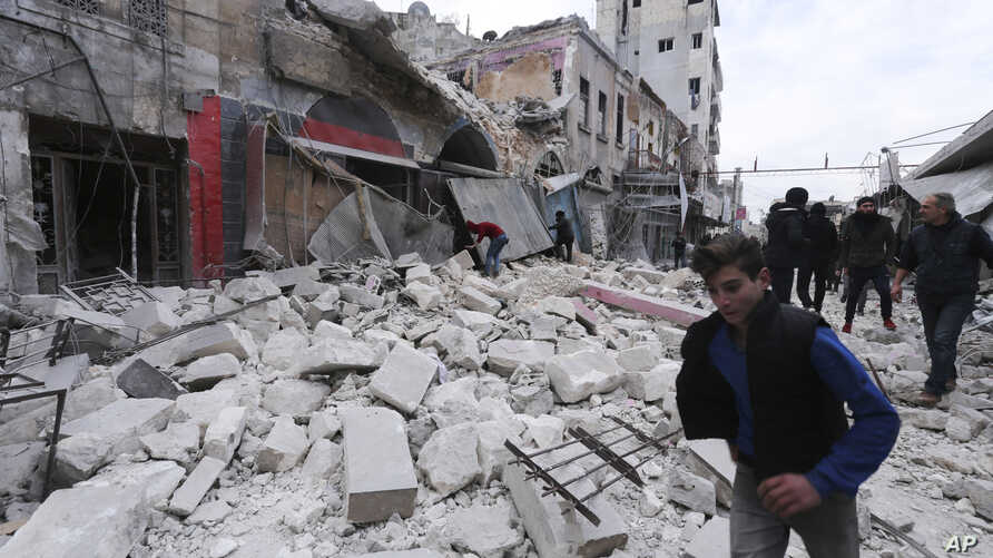 FILE - People walk past debris following airstrikes by government forces, in the town of Ariha, Idlib province, Syria, Jan. 15, 2020.