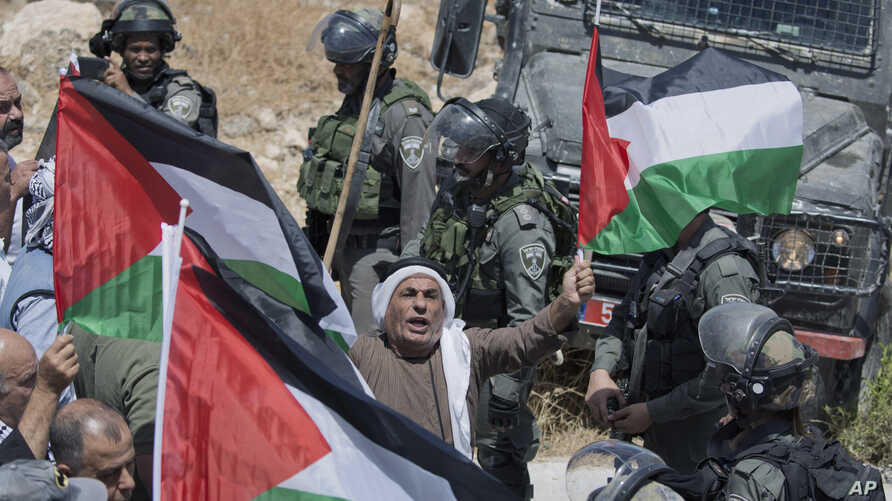 Israeli border police block the road and disperse Palestinian, Israeli and foreign activists during a rally protesting a newly established settlement near the West Bank village of Kufr Malik, East of Ramallah, Aug. 16, 2019.