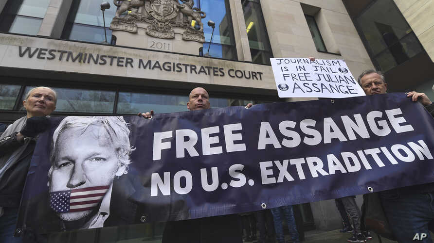Demonstrators stand outside Westminster Magistrates Court in support of WikiLeaks founder Julian Assange, who is due to appear for an administrative hearing, in London, Jan. 13, 2020.