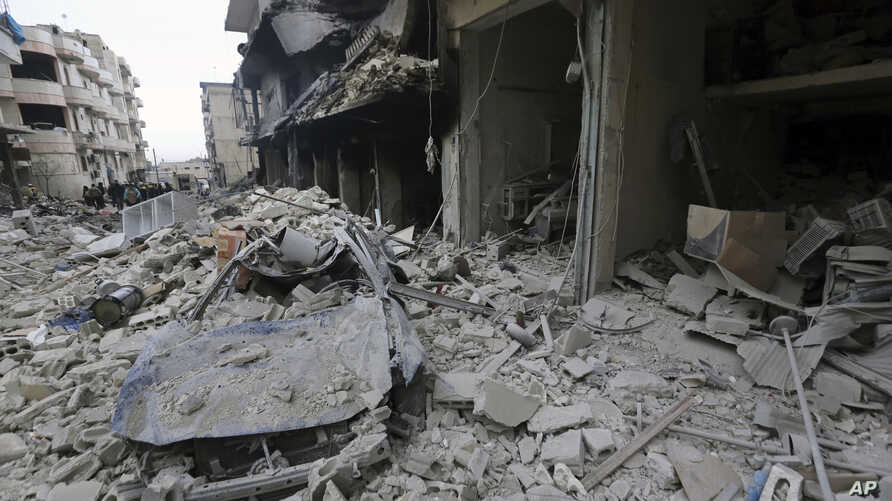 People inspect a damaged site after airstrikes on the town of Ariha, in Idlib province, Syria.