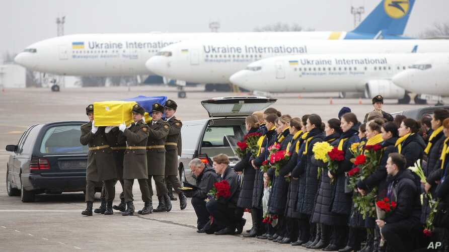 In this photo provided by the Ukrainian Presidential Press Office, honor guard carry a coffin of the one of the eleven Ukrainian victims of the Boeing 737-800 plane at Borispil international airport outside Kyiv, Jan. 19, 2020.