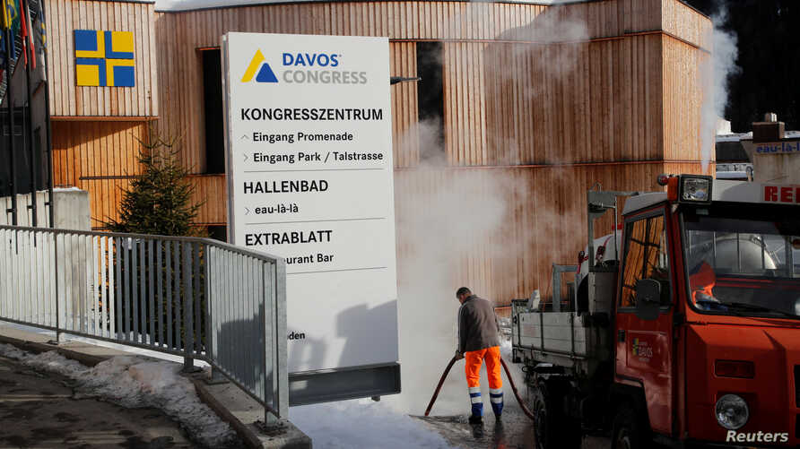 FILE - A worker uses steam to remove ice from a footpath in front of one of the venues of the World Economic Forum (WEF) in Davos, Switzerland, Jan. 13, 2020.