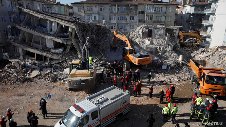 Emergency personnel work at the site of damaged buildings after an earthquake in Elazig, Turkey, Jan. 27, 2020.