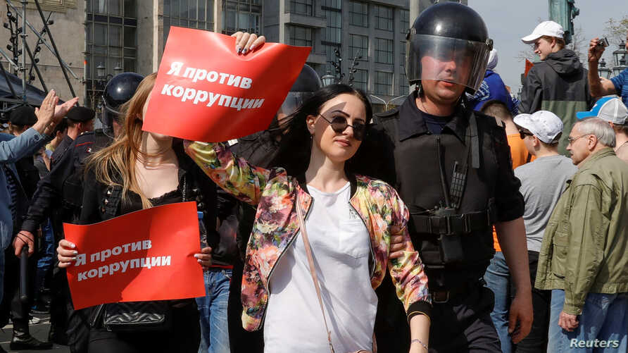 """FILE - Policemen detain demonstrators during a protest in Moscow, Russia, May 5, 2018. The posters reads """"I am against corruption."""""""