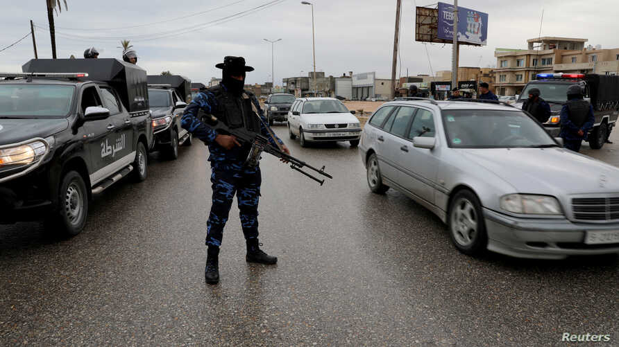 FILE - A member of the central security support force holds a weapon during a security deployment in the Tajura neighborhood, east of Tripoli, Libya, Dec. 30, 2019.