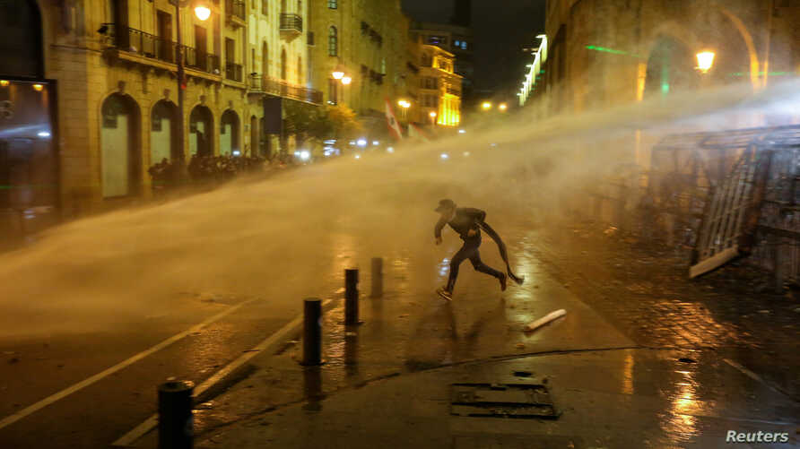 A demonstrator is hit by a water cannon during a protest against a ruling elite accused of steering Lebanon towards economic crisis in Beirut.