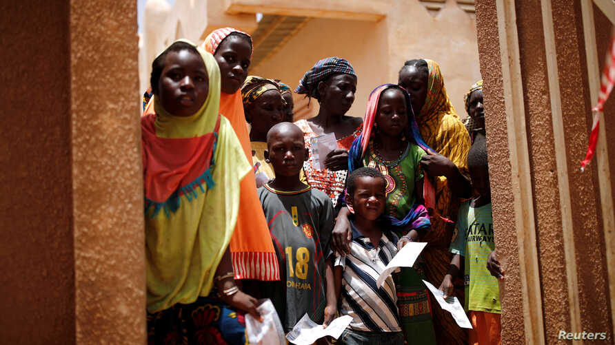 Local women and children arrive at an abandoned clinic to receive medical care from the French military during Operation Barkhane in Ndaki, Mali, July 29, 2019.