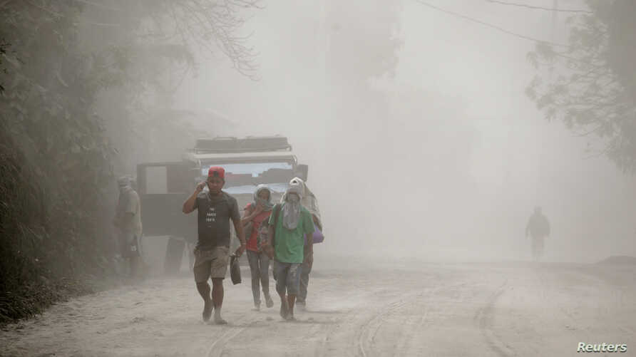 Residents living near the erupting Taal Volcano evacuate in Agoncillo, Batangas, Philippines, Jan. 13, 2020.