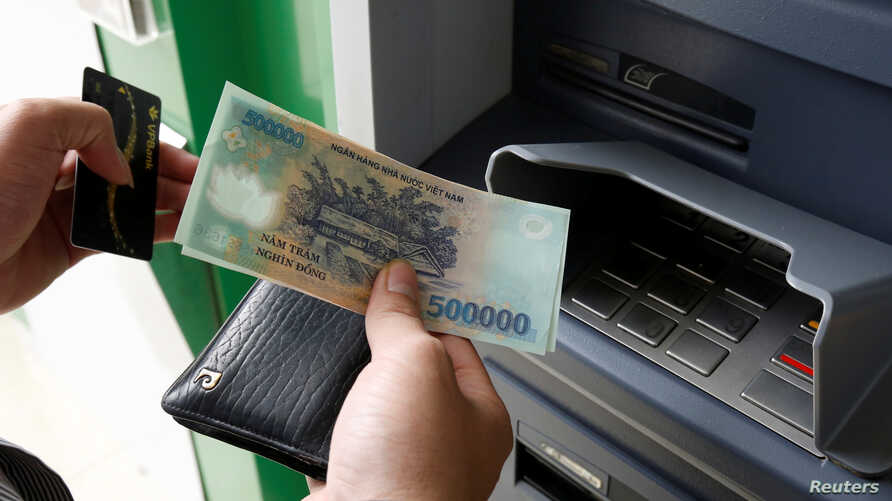 FILE - A man withdraws money from an ATM at a branch of Vietnam Prosperity Joint Stock Commercial Bank (VPBank) in Hanoi, Nov. 15, 2017.