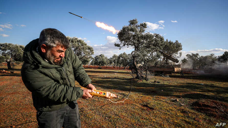 A Syrian rebel fighter remotely-fires a rocket from a truck-mounted launcher at a position in the countryside of Idlib towards…