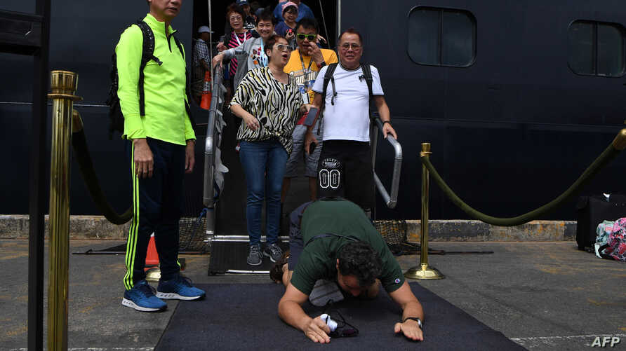 A passenger reacts as he disembarks from the Westerdam cruise ship in Sihanoukville on February 14, 2020, where the liner…
