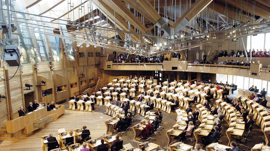 FILE - In this Sept. 7, 2004 file photo, Scottish lawmakers settle into their stylish, ergonomic seats at the new Scottish…