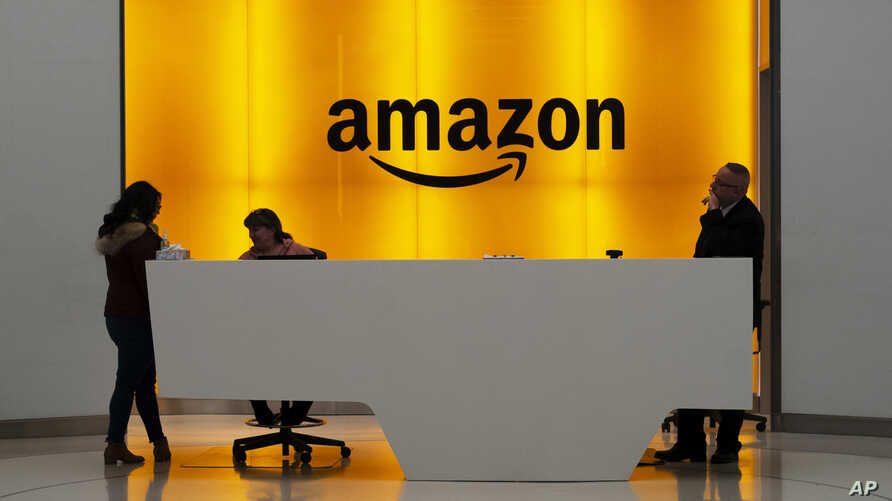 FILE - In this Feb. 14, 2019, file photo people stand in the lobby for Amazon offices in New York. Amazon says President Donald…