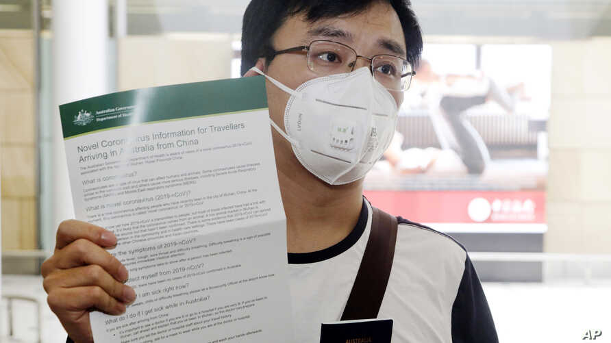 Passenger Kevin Ouyan shows an information pamphlet he was given on arrival at Sydney airport in Sydney, Jan. 23, 2020, on a flight from Wuhan, China.
