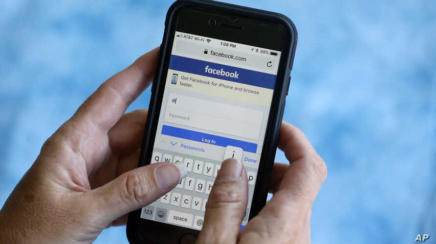 FILE - Facebook start page is shown on a smartphone in Surfside, Fla.