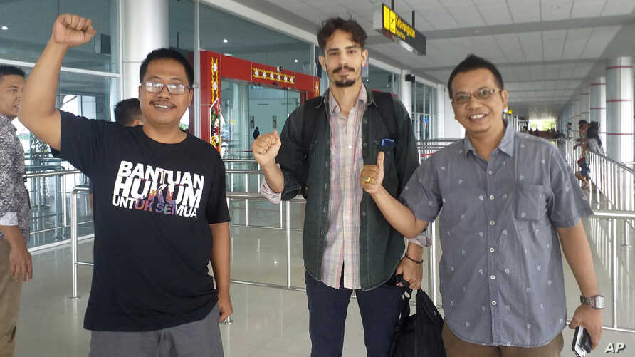 American journalist Philip Myrer Jacobson, center, poses with his Indonesian lawyers at Cilik Riwut Airport in Palangkaraya, Indonesia, Jan. 31, 2020.