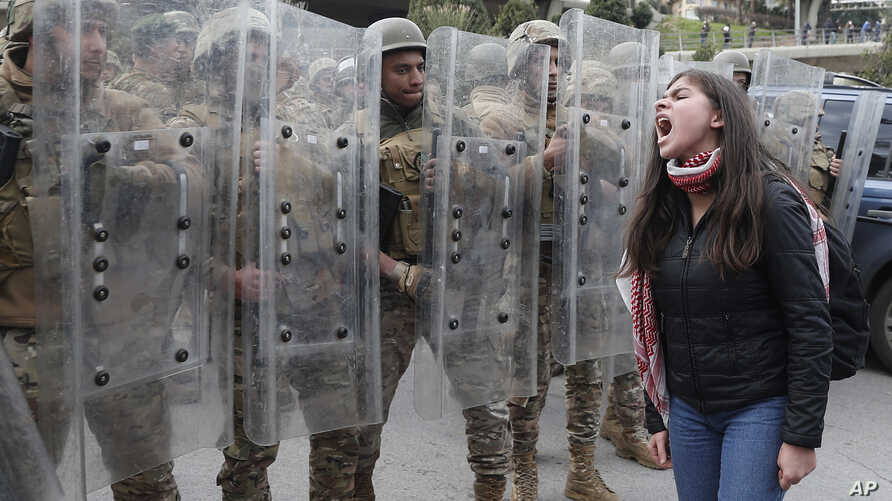 A protester shouts slogans in front of army soldiers during a protest against a parliament session vote of confidence for the…