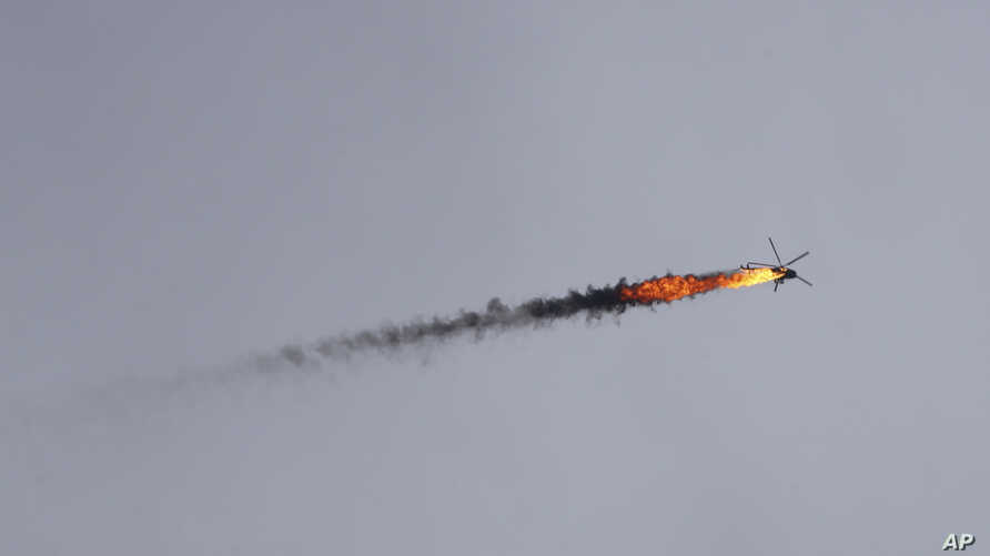 Syrian government helicopter is shot by a missile in Idlib province, Syria, Tuesday, Feb. 11, 2020. Syrian rebels shot down a…