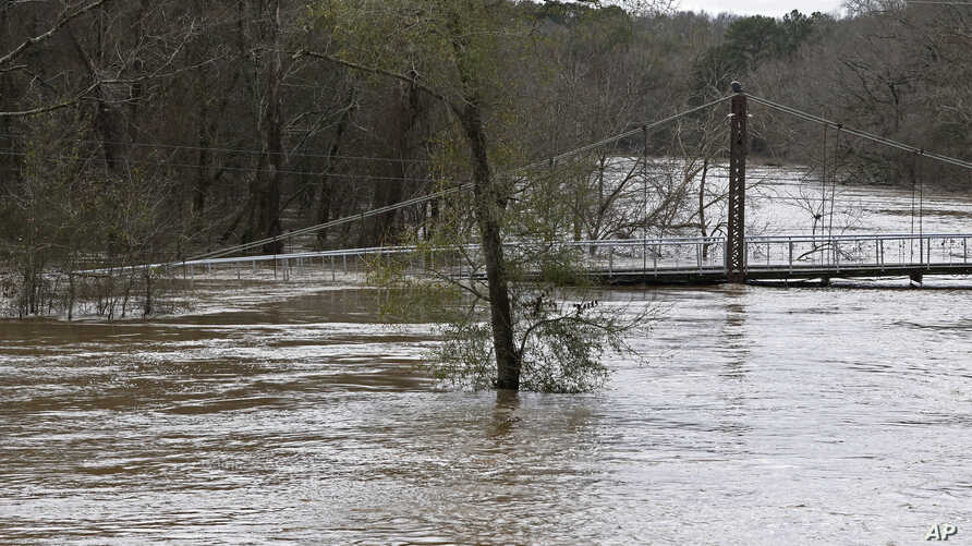 Water from the Pearl River floods Byram Swinging Bridge, which connects Hinds and Rankin Counties in Byram, Miss., Monday, Feb…