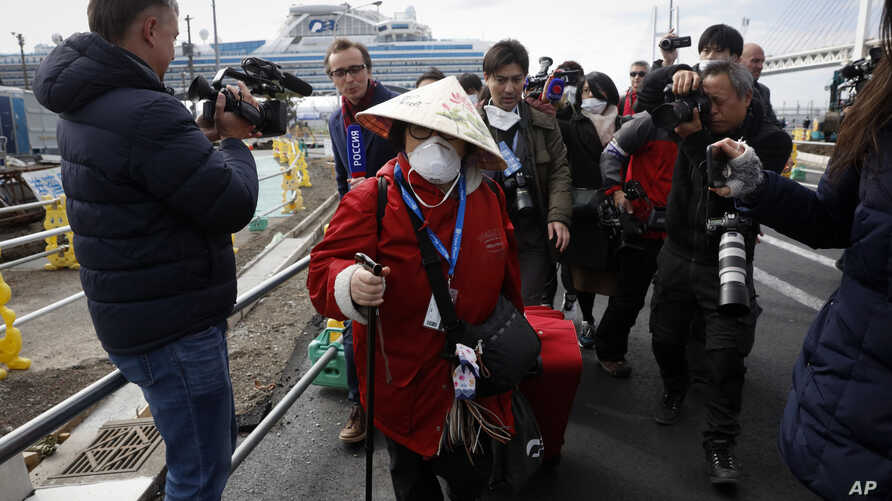 An unidentified passenger is surrounded by the media after she disembarked from the quarantined Diamond Princess cruise ship.