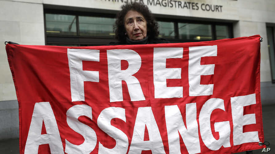 A demonstrator holds a banner outside Westminster Magistrates Court in London, Wednesday, Feb. 19, 2020. A case-management…
