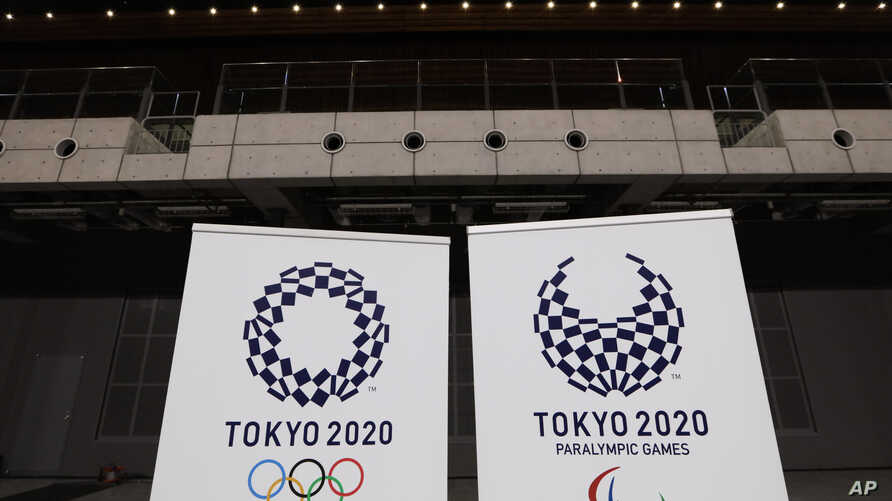 FILE - In this Feb. 2, 2020, file photo, two logo for the Tokyo 2020 Olympics and Paralympics, are displayed at a grand opening…