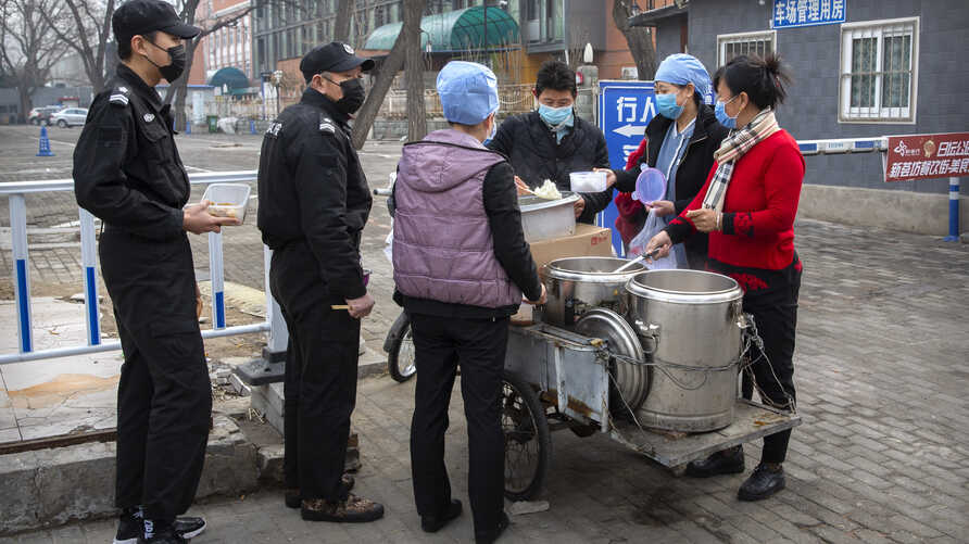 Security guards line up as workers in face masks dispense lunch outside of an office building in Beijing, Feb. 21, 2020.