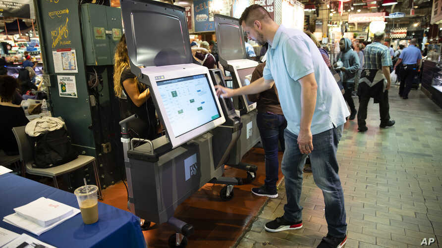 FILE - Steve Marcinkus, an Investigator with the Office of the City Commissioners, demonstrates the ExpressVote XL voting machine at the Reading Terminal Market in Philadelphia, June 13, 2019.