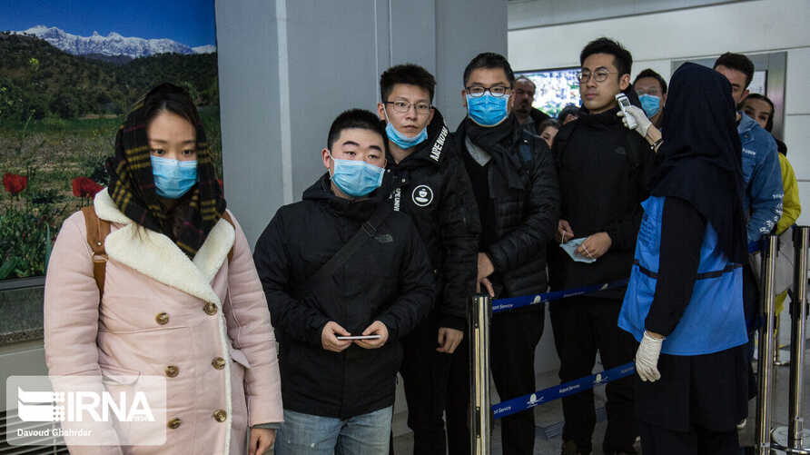 Chinese travelers wearing face masks to protest against the coronavirus undergo a health screening upon arrival at an Iranian ai