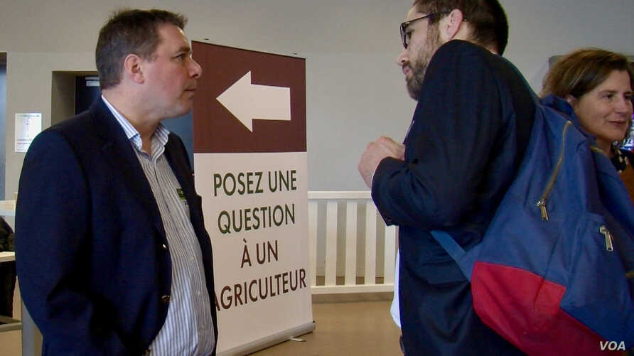 Farmer Jerome Regnault, left, answers questions posed by Germain Milet, right, about his trade. (Lisa Bryant/VOA)