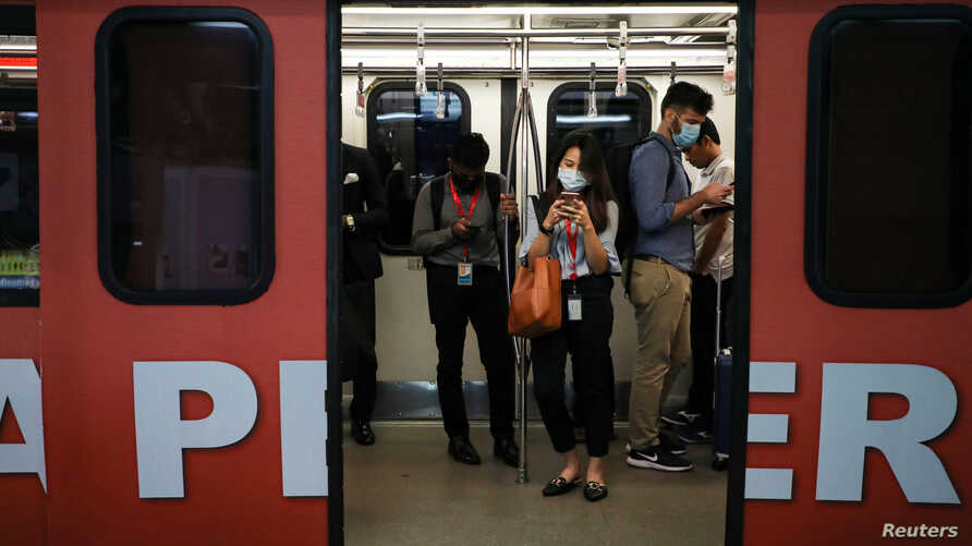 Passengers wear masks to protect themselves from coronavirus in a Light Rail Transit train in Kuala Lumpur, Malaysia, February…