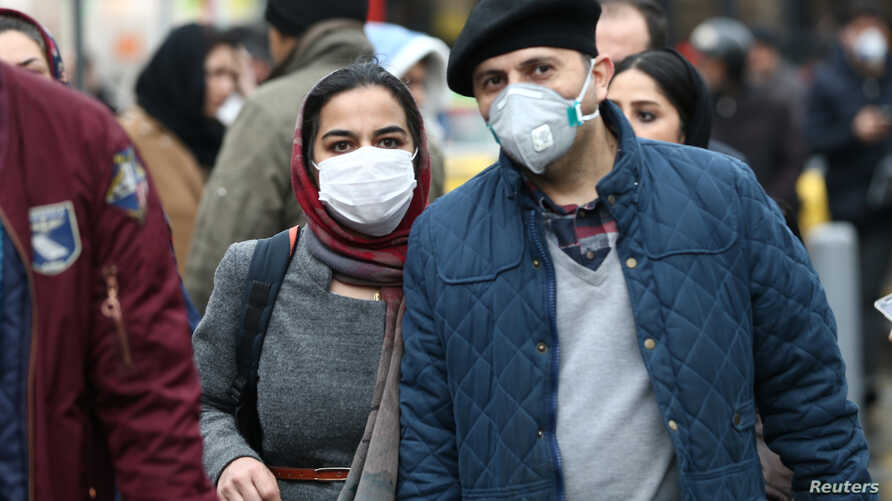 Iranian couple wearing protective masks to prevent contracting a coronavirus walk at Grand Bazaar in Tehran, Iran, Feb. 20, 2020.