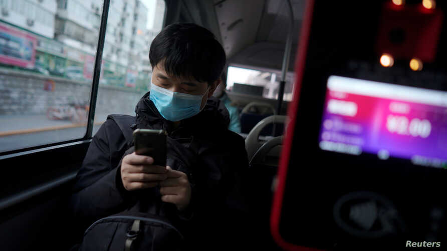 A passenger wearing a face mask checks his mobile phone on a bus, following an outbreak of the novel coronavirus in the country…