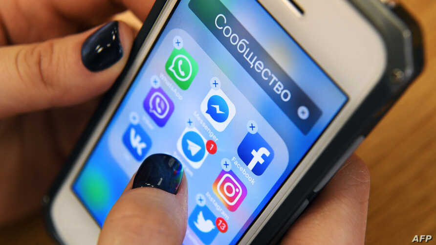 FILE - A woman holds a smartphone with the icons for the social networking apps, including Facebook, in Moscow, Russia, March 23, 2018.