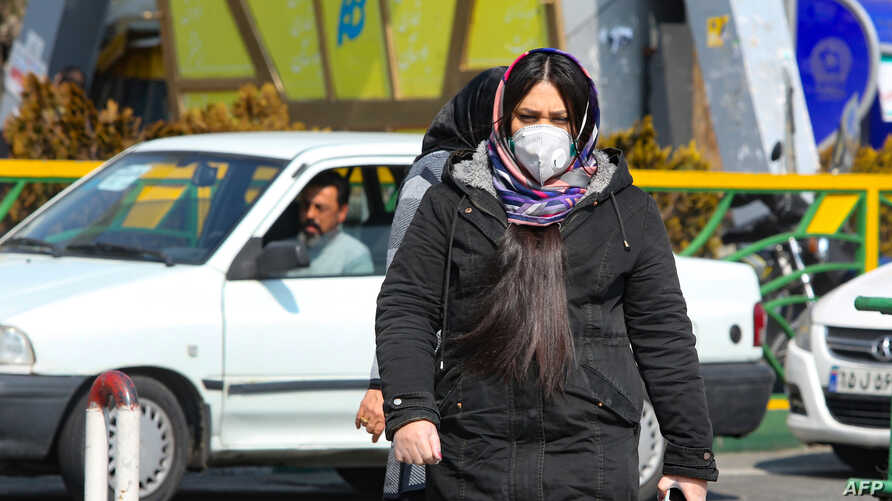 A woman wearing a protective mask crosses a street in Iran's capital Tehran, Feb. 22, 2020.