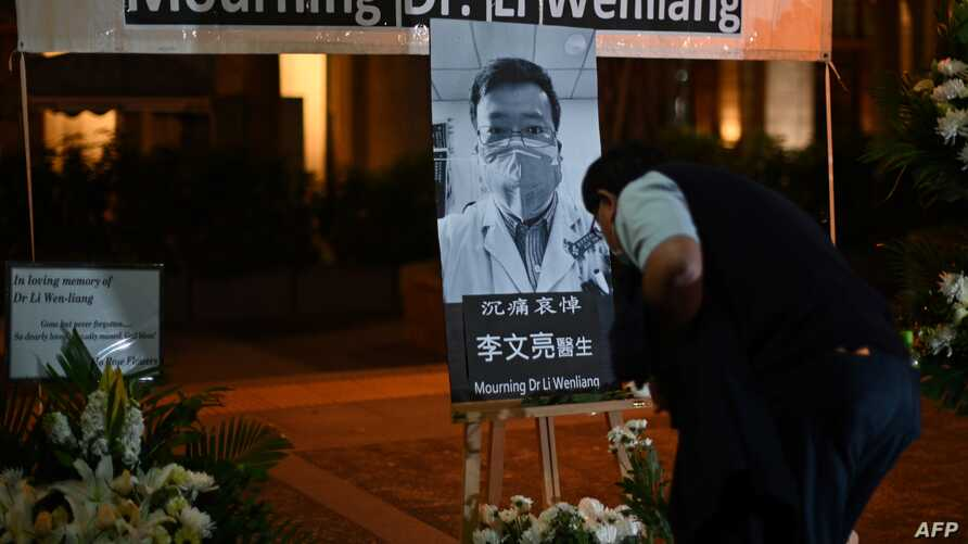 People attend a vigil in Hong Kong for novel coronavirus whistleblowing doctor Li Wenliang, 34, pictured center, who died Friday, Feb. 7, in Wuhan after contracting the virus while treating a patient.